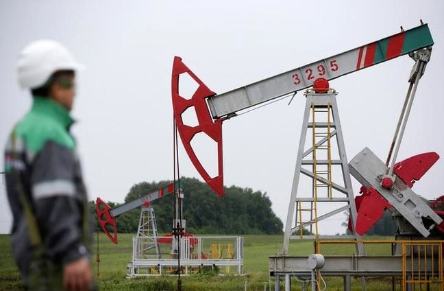 Oil surges after output cuts, strong dollar weighs